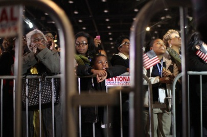 People listen to Barack Obama speak at his campaign's election night party
