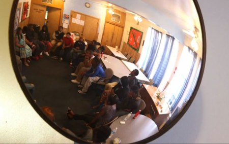 A mirror above the room in the New Life Baptist Church in Roseland, Chicago, reflects a circle of youth discussing the effect of gun violence in their lives.
